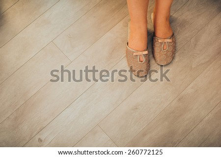 woman in slippers sitting on the bed - stock photo