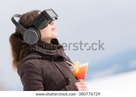 woman in snow is wearing virtual reality glasses and dreams of summer holiday with a cocktail in her hand