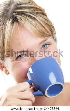 Woman in soft light drinking coffee from a blue cup