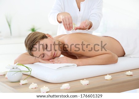 Woman in spa institute receiving oil massage - stock photo