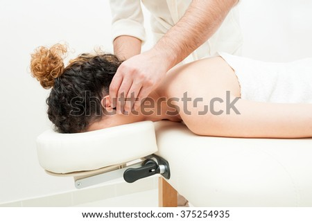 Woman in spa salon having ears massage and lying on massage table - stock photo