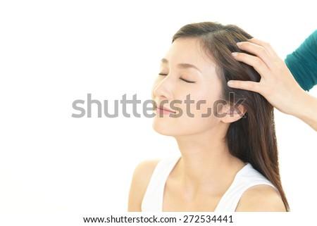 Woman in spa salon receives head massage - stock photo