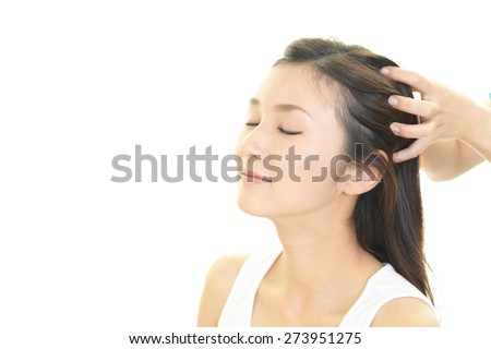 Woman in spa salon receives head massage - stock photo