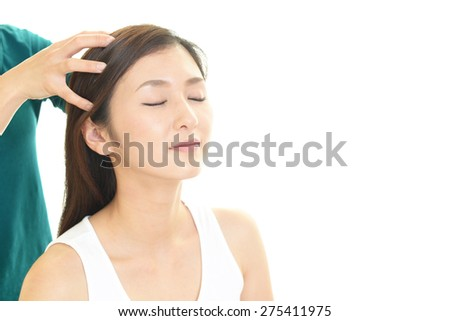 Woman in spa salon receives head massage