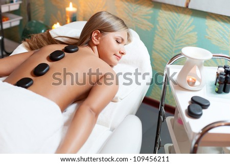 woman in spa salon receives spa stones massage - stock photo