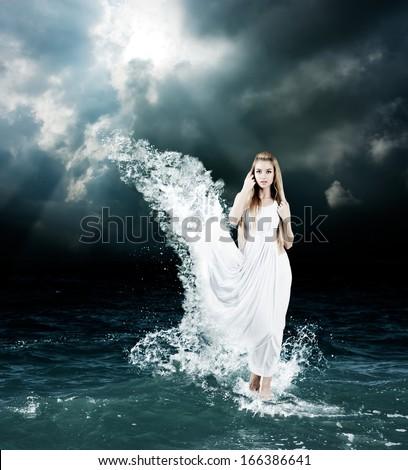 Woman in Splashing Dress Walking on Stormy Sea. Aphrodite Godess Collage. - stock photo