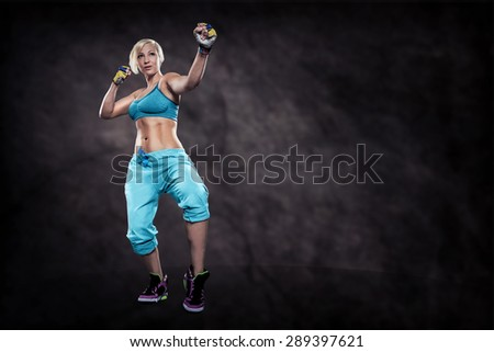 woman in sport dress at boxing exercise on the night street - stock photo
