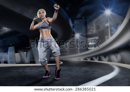 woman in sport dress at piloxing exercise on the night street - stock photo