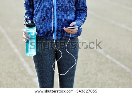 Woman in sports clothes and sneakers with cellphone and bottle - stock photo