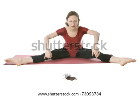 Woman in sports clothes reaching for a chocolate bar - stock photo