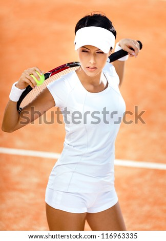 Woman in sports wear keeps tennis racket and ball on her shoulders at the clay tennis court. Tournament - stock photo