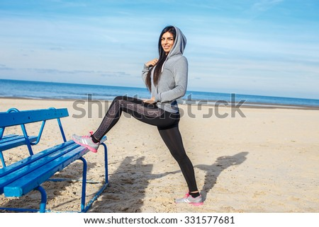 Woman in sportswear doing flexible exercises on a beach near blue bench. - stock photo