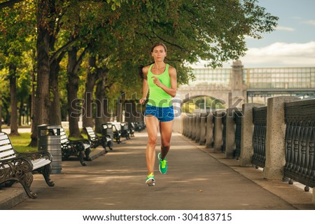 woman in sportswear jogging in the park at sunny day