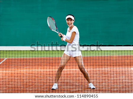 Woman in sportswear plays tennis at training - stock photo