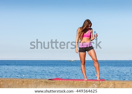 Woman in sportswear takes a break to rehydrate drinking water from plastic bottle, resting after sport workout outdoor by seaside