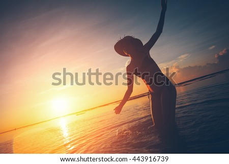 Woman in straw dancing in the ocean while the sun rising