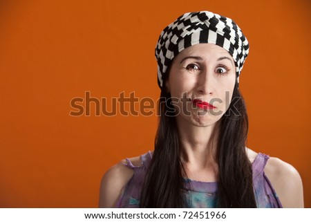 Woman in striped cap and tie-die making faces - stock photo