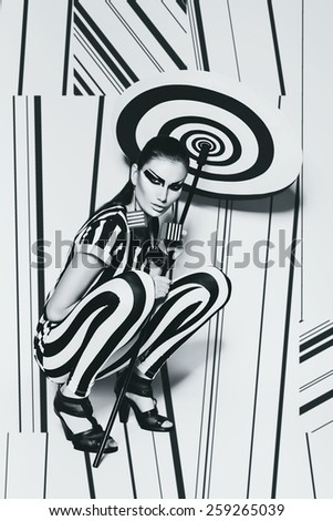 woman in striped top sitting with umbrella on striped background in studio - stock photo