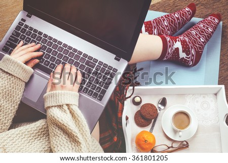 Woman in stylish casual sweater with a laptop on her lap typing on the keyboard and having sweet breakfast with the cup of coffee. The concept of personal productivity and work remotely - stock photo