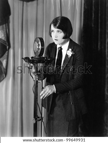 Woman in suit at microphone - stock photo