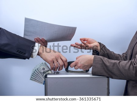 Woman in suit giving briefcase with dollars to man