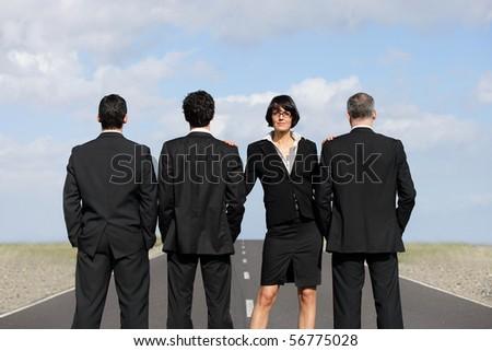 Woman in suit standing near men in suit - stock photo