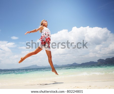Woman in summer dress jumping over wet sand by tropical sea - stock photo