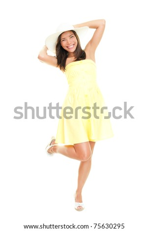 Woman in summer dress playful and cheerful. Isolated on white background in full length. Beautiful fresh young mixed race ethnic female model in yellow dress and summer hat. - stock photo