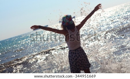 Woman in summer dress standing on a sea coast and looking to the horizon, Spray waves Storm - stock photo
