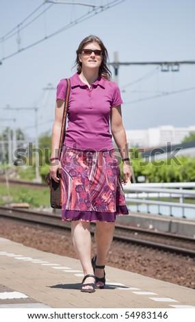 Woman in summer dress walking on platform - stock photo