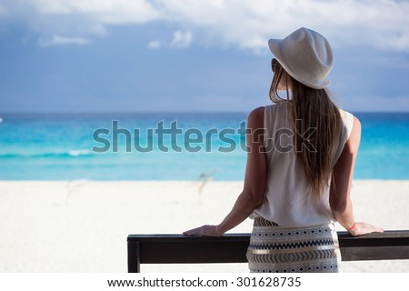 Woman in summer hat on balcony looking to the turquoise sea and white perfect sandy beach, enjoying life and summer vacation, rear view - stock photo