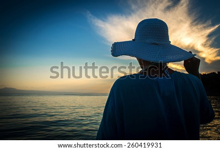 Woman in summer hat standing on a sandy beach and looking to the - stock photo