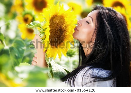Woman in sunflower field - rural life and aromatherapy concept - stock photo