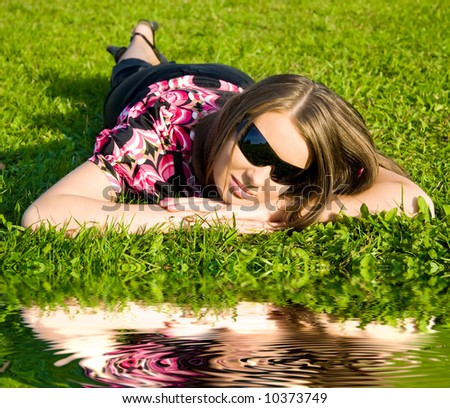 Woman in sunglasses resting on a green grass. Soft reflection in a water. - stock photo