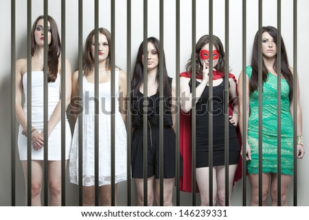 Woman in superhero costume with female friends standing behinds prison bars - stock photo
