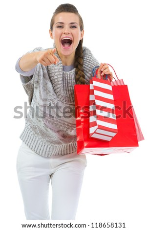 Woman in sweater with shopping bags pointing in camera - stock photo