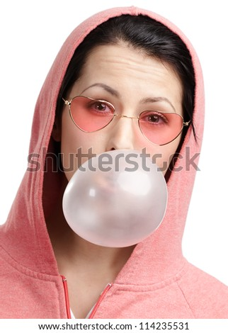 Woman in sweatshirt and heart shaped glasses blows out pink bubble gum, isolated on white - stock photo