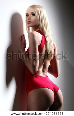 Woman in swimsuit. Fit body. Slim and muscular tanned young fitness woman. Beautiful model girl with perfect fashion makeup and hairstyle. A photo of beautiful girl is in fashion style. - stock photo