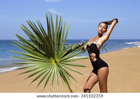 Woman in swimsuit on beach near sea with palm branch enjoying sun. Hair up. Tropics. Hot summer day. Sexy girl. Vacation. Photo from Phuket island. Thailand - stock photo