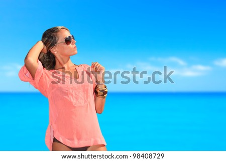 Woman in swimsuit on the beach enjoying the summer by the sea - stock photo