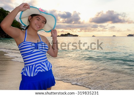 Woman in swimsuit standing poses on beach with happy and beautiful sky above the sea during sunrise at Honeymoon Bay, Koh Miang Island, Similan National Park, Phang Nga, Thailand - stock photo