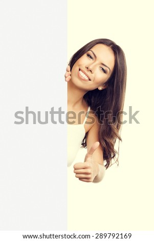 woman in tank top casual smart clothing, showing thumb up hand sign gesture, over empty blank signboard with copyspace area for text or slogan - stock photo