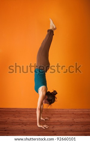 Woman in the Adho Mukha Vriksasana Yoga position - stock photo
