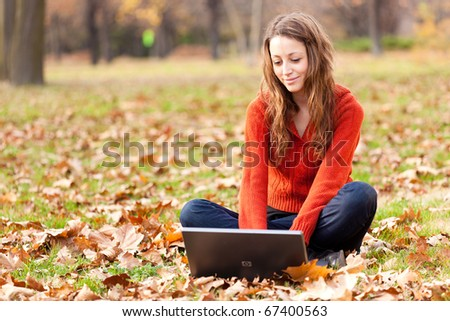 Woman in the autumn park working on laptop - stock photo