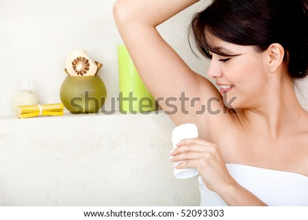 Woman in the bathroom putting deodorant on her armpit - stock photo