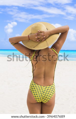 Woman in the beach wearing a hat in Playa del Carmen, Mexico.