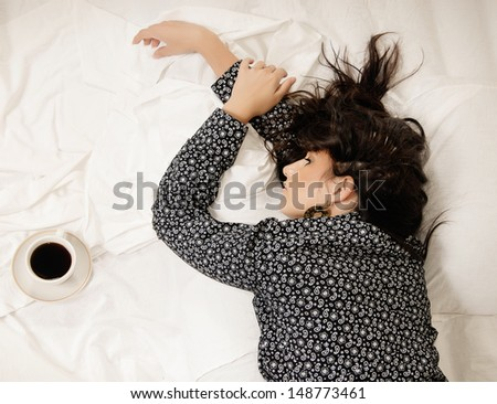 Woman in the bed with coffee - stock photo