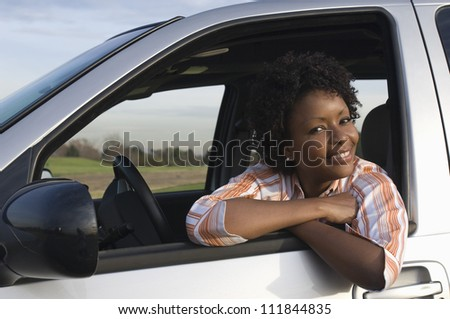Woman in the car and looking away - stock photo