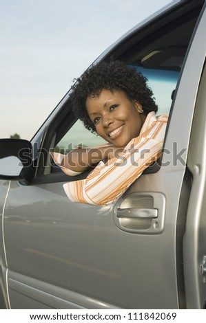 Woman in the car smiling - stock photo