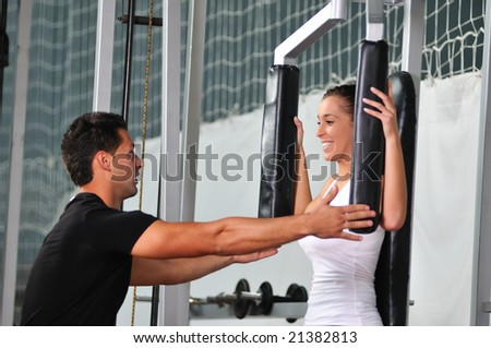 woman in the fitness gim working out with personal trainer coach - stock photo